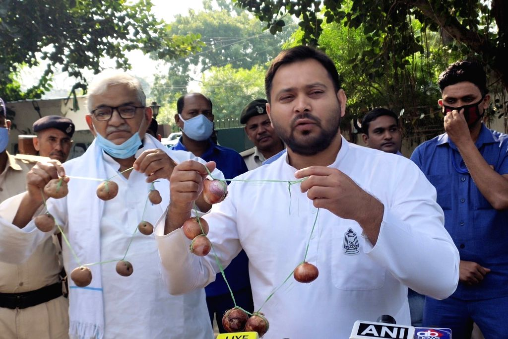 RJD leader Tejashwi Yadav holds a garland of onions as he talks to the media during his party's protest against hike in the prices of vegetables, in Patna on Oct 26, 2020. - Tejashwi Yadav