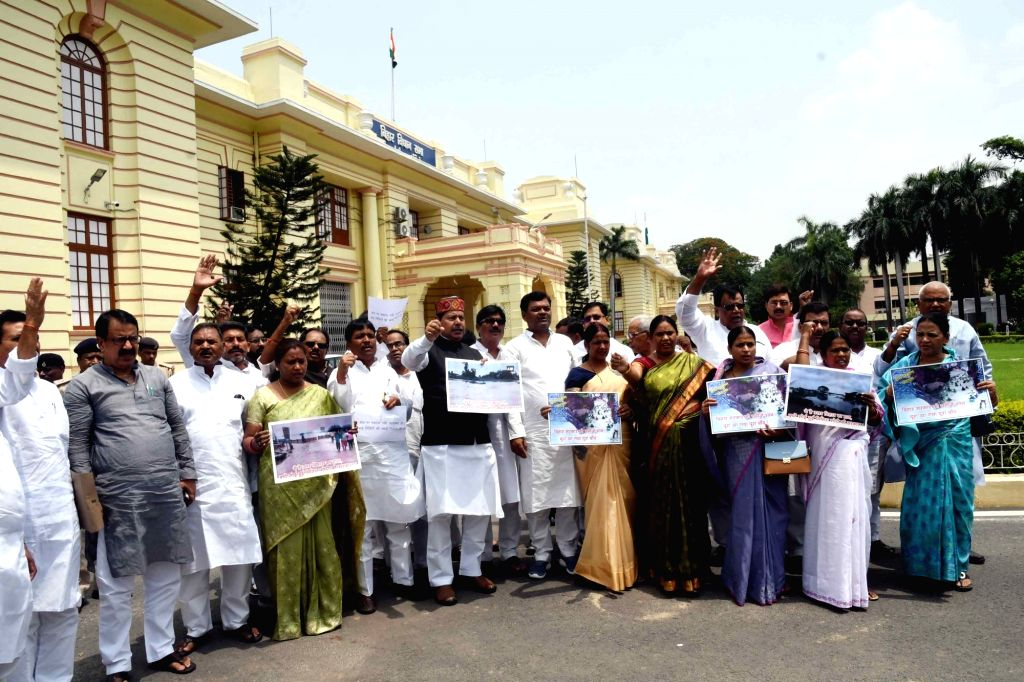 RJD legislators stage a demonstration over the situation of flood in Bihar, at state assembly in Patna on July 17, 2019.