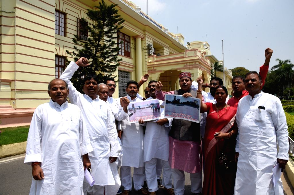 RJD legislators stage a protest against Bihar government urging it to deal with flood situation in the state on a war footing, at Bihar Assembly in Patna on July 16, 2019.