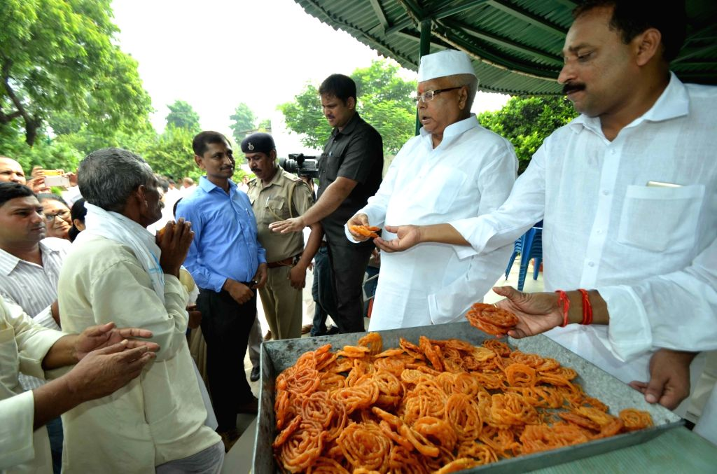 RJD supremo Lalu Yadav distributes sweets at his residence on Independence Day in Patna on Aug 15, 2016. - Lalu Yadav