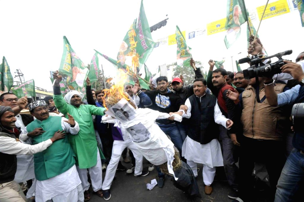 RJD workers burn the effigy of RSS chief Mohan Bhagwat as they stage a demonstration in Patna on Feb 13, 2018.