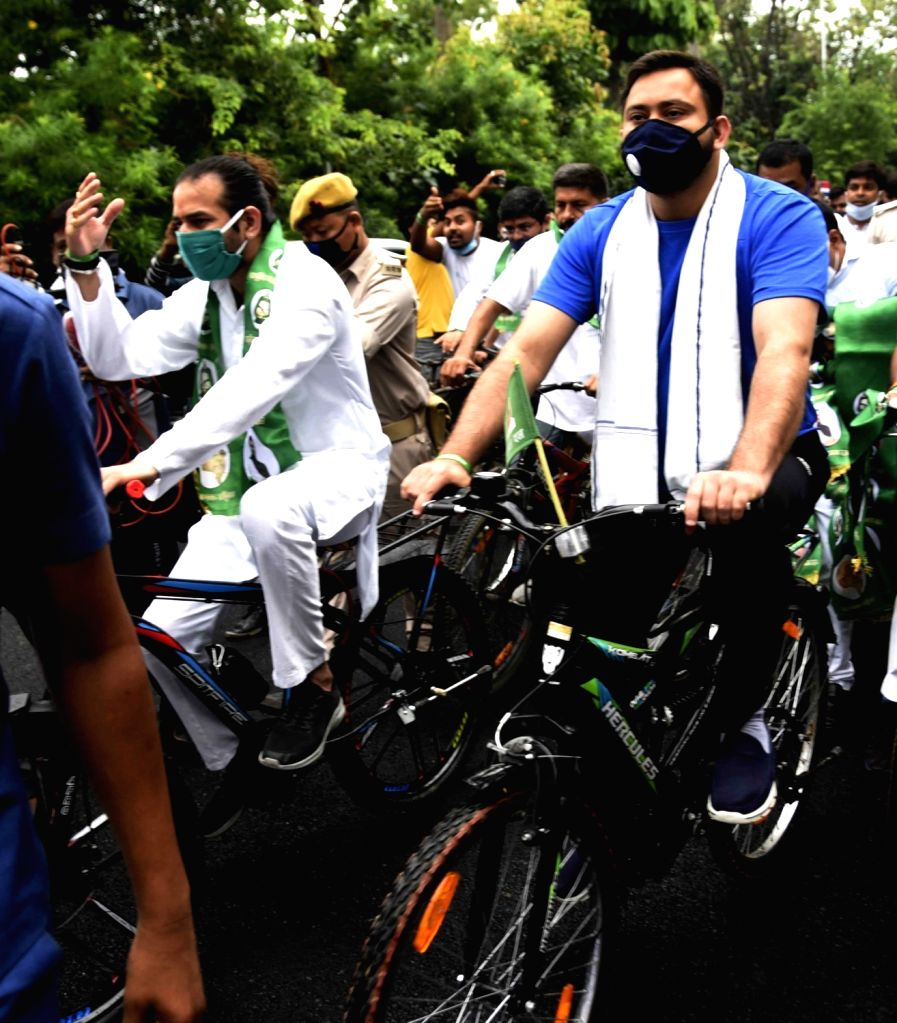 RJD workers led by party leaders Tej Pratap Yadav and Tejashwi Yadav, participate in a cycle rally to protest against hike in the prices of petrol and diesel, in Patna on June 25, 2020. - Tej Pratap Yadav and Tejashwi Yadav