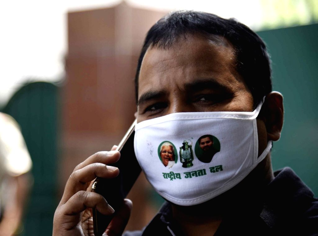 RJD workers wear masks bearing the party's name and photos of its leaders Lalu Prasad Yadav and Teashwi Yadav along with the party symbol, at the party's 24th Foundation Day function, in Patna ... - Lalu Prasad Yadav and Teashwi Yadav