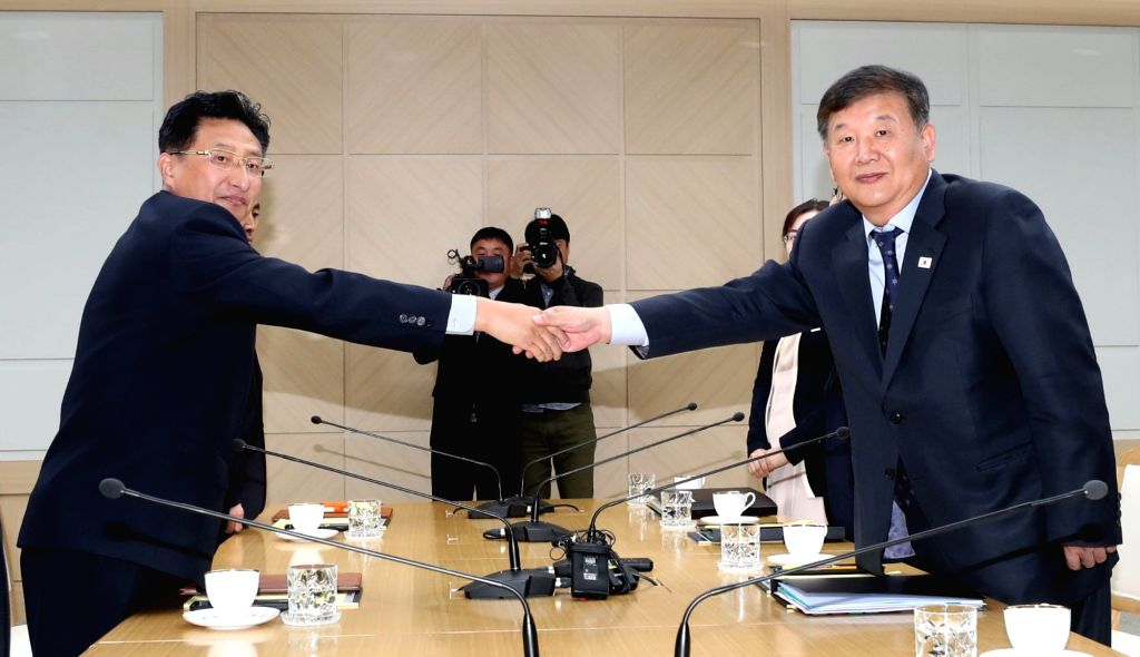 Roh Tae-kang (R), South Korea's vice minister of culture and sports, and his North Korean counterpart Won Kil-u shake hands at the start of their talks at the inter-Korean liaison office in ...
