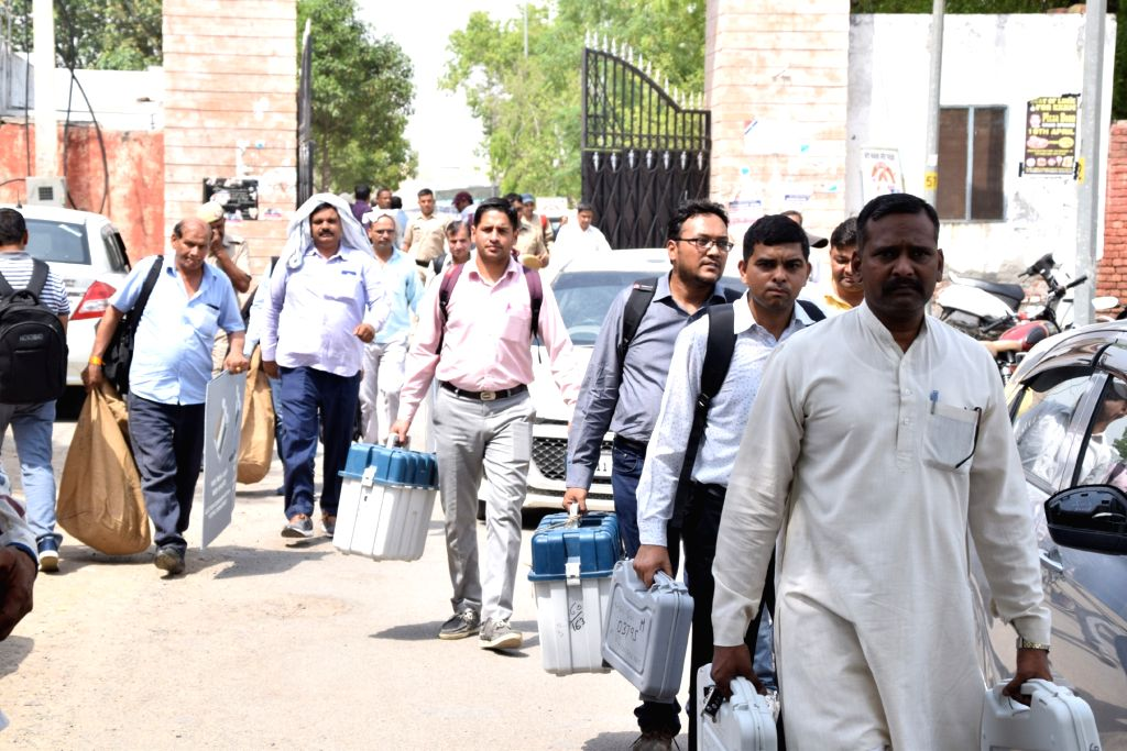 Rohtak: Polling officials carrying the Electronic Voting Machine (EVMs) and other necessary inputs required for 2019 Lok Sabha elections, leave for their respective polling stations from the distribution centre in Rohtak, Haryana on May 11, 2019. (Ph