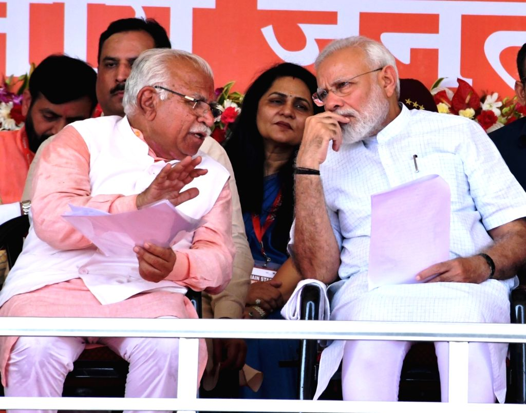 Rohtak: Prime Minister Narendra Modi interacts with Haryana Chief Minister Manohar Lal Khattar during a rally ahead of the upcoming Haryana Assembly Elections in Rohtak, Haryana on Sep 8, 2019. (Photo: IANS) - Narendra Modi and Manohar Lal Khattar