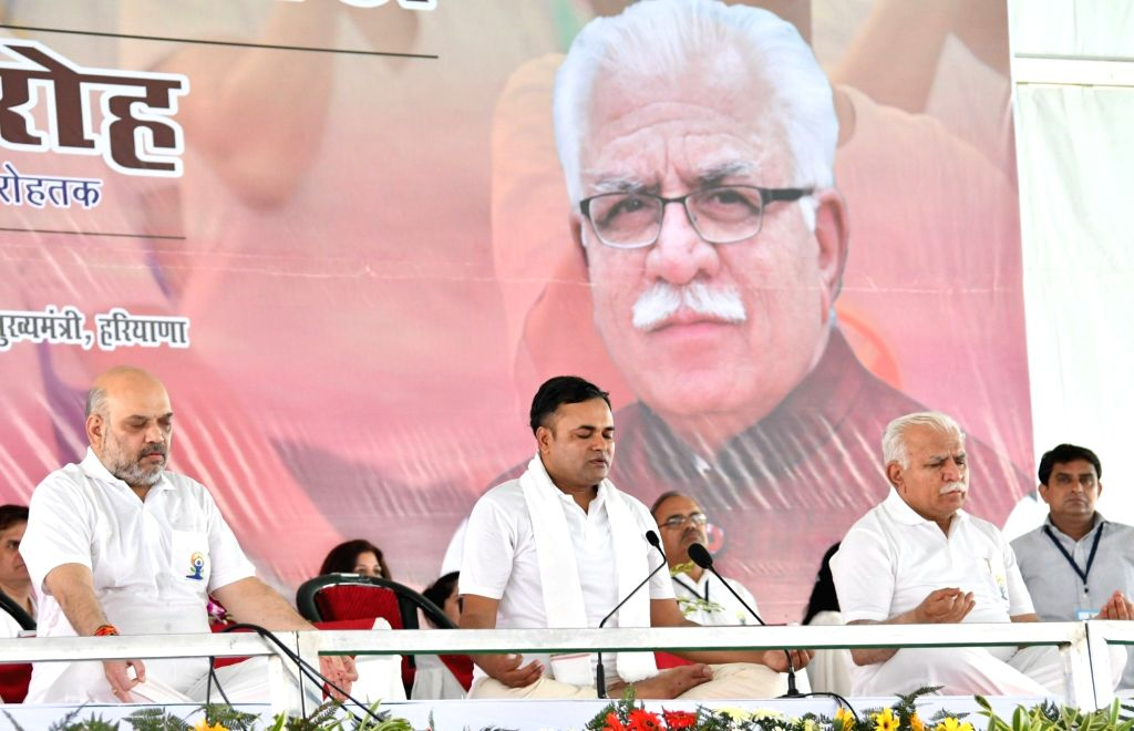 Rohtak: Union Home Minister Amit Shah and Haryana Chief Minister Manohar Lal Khattar perform yoga asanas -postures- on the 5th International Yoga Day, in Rohtak on June 21, 2019. (Photo: IANS) - Amit Shah and Manohar Lal Khattar