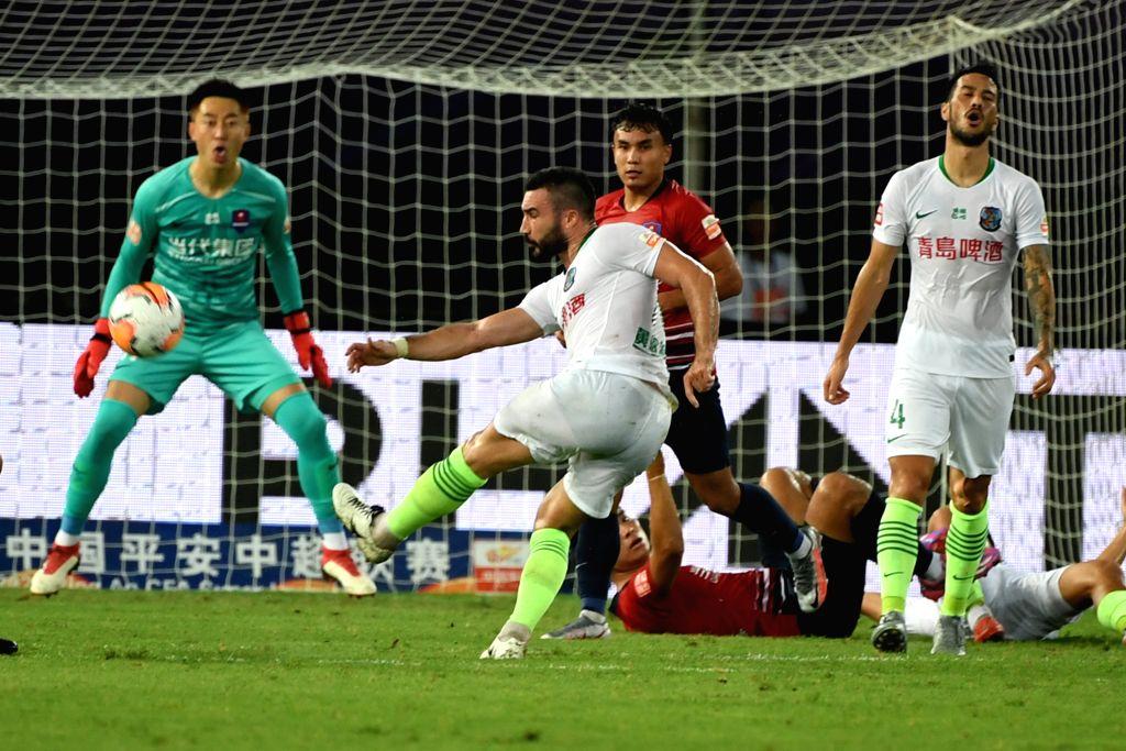 Romain Alessandrin (2nd L) of Qingdao Huanghai shoots during the 4th round match between Chongqing Dangdai Lifan and Qingdao Huanghai at the postponed 2020 season ...