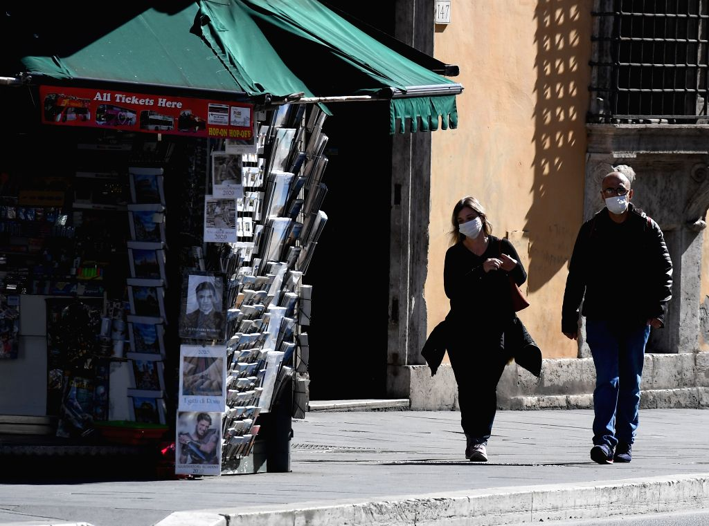 ROME, March 12, 2020 (Xinhua) -- People wearing face masks walk on a street in Rome, Italy, on March 12, 2020. Italian Prime Minister Giuseppe Conte on Wednesday evening announced the closure of all retail shops, coffee bars, pubs, restaurants, hair  - Giuseppe Conte