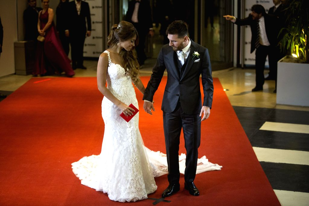 ROSARIO, July 1, 2017 - Argentine soccer player Lionel Messi(R) holds his wife Antonela Roccuzzo's hand at their wedding in Rosario, Argentina, June 30, 2017. /IANS)