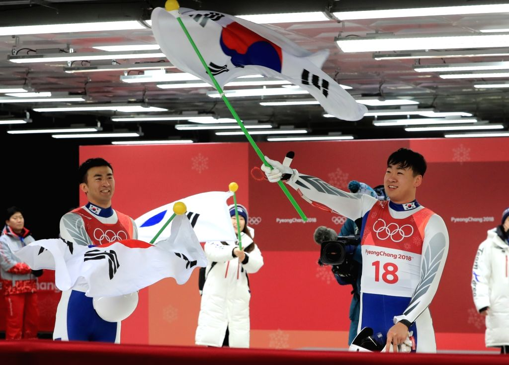 S. Korean luge team Park Jin-yong (R) and Cho Jung-myung wave their country's national flag after their race in men's doubles of PyeongChang Winter Olympics at the games' main host city ...