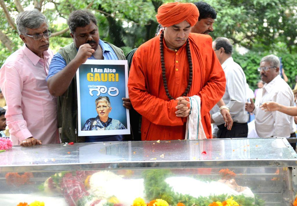 "Sadhus pay tribute during the public viewing of the mortal remains of Gauri Lankesh in Bengaluru on Sept 6, 2017. Editor of the weekly Kannada tabloid ""Lankesh Patrika"", Lankesh ..."