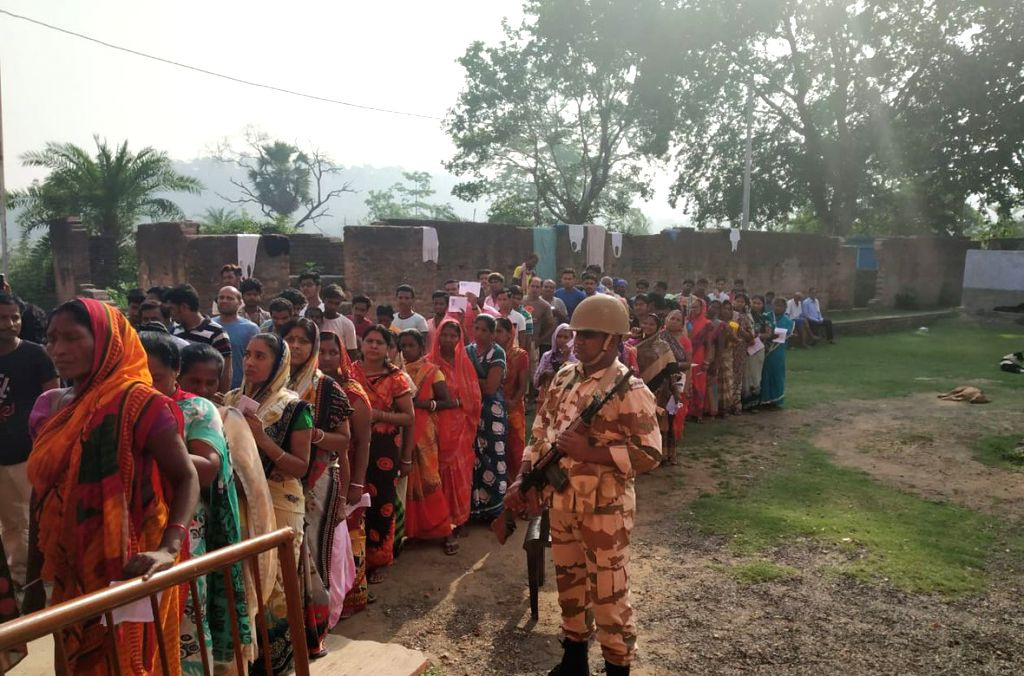 Sahibganj: A soldier stands guard as people wait in queue to cast votes during the seventh and the last phase of 2019 Lok Sabha Elections at a polling booth in Sahibganj, Jharkhand, on May 19, 2019. (Photo: IANS/ITBP)