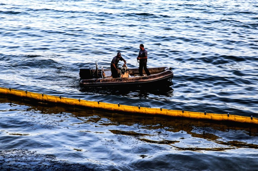 SALAMINA ISLAND (GREECE), Sept. 13, 2017 Cleaning crew members try to clean up leaking oil near Salamina island, Greece on Sept. 12, 2017. Greek authorities were racing against time on ...