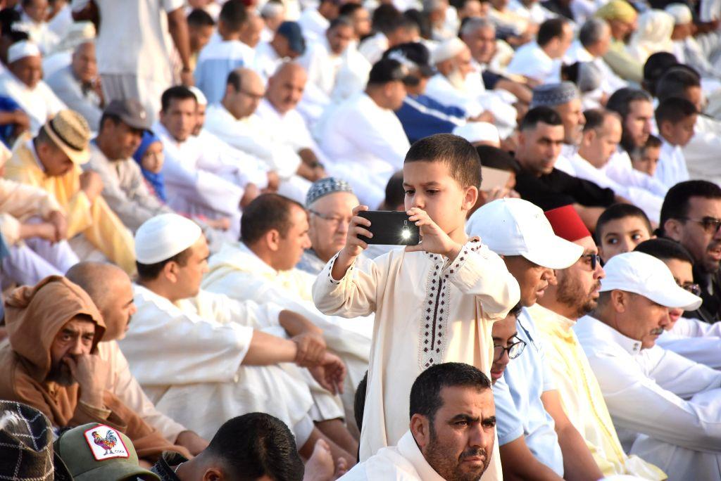 SALE (MOROCCO), Aug. 12, 2019 A boy takes photos during the Eid al-Adha prayer in Sale, Morocco, on Aug. 12, 2019.