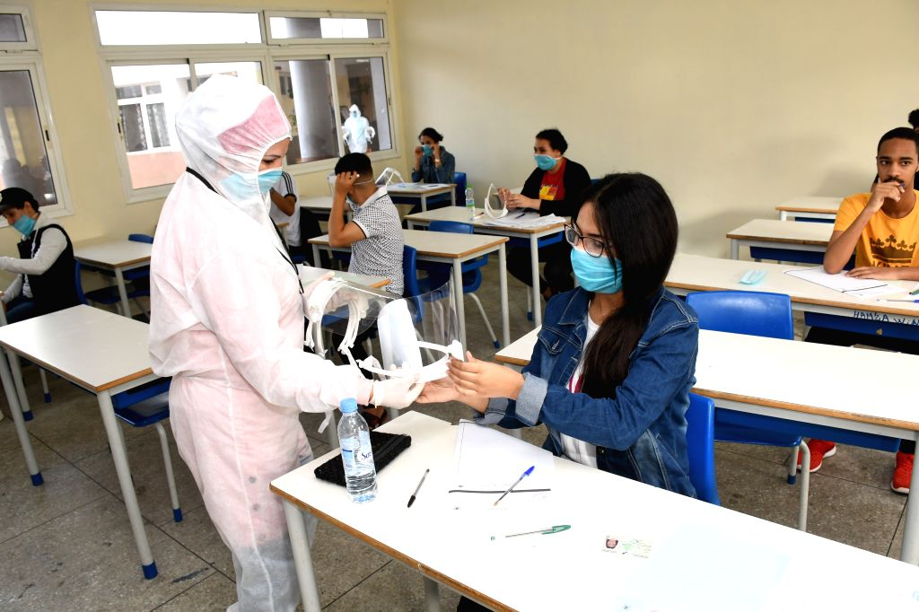 Sale (Morocco), July 3, 2020 A staff member distributes a shield to a student before a college entrance exam in Sale, Morocco, on July 3, 2020. A total of 319 new COVID-19 cases were ...