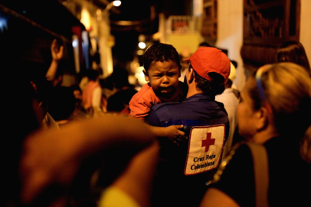 A minor is attended by a Red Cross worker in a temporary shelter after a landslide in the municipality of Salgar, department of Antioquia, northwest Colombia, on May ...