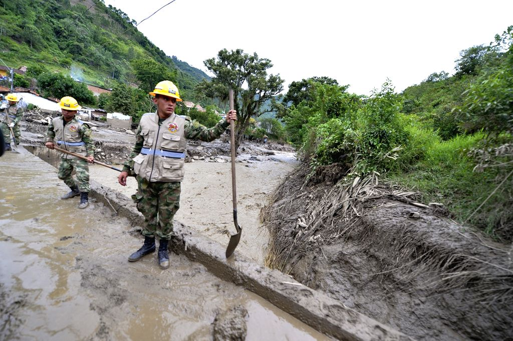 Image provided by Colombia's Defense Ministry shows soldiers cleaning a road after a mudslide in Salgar Municipality of northwest Colombia's Antioquia Department May ...