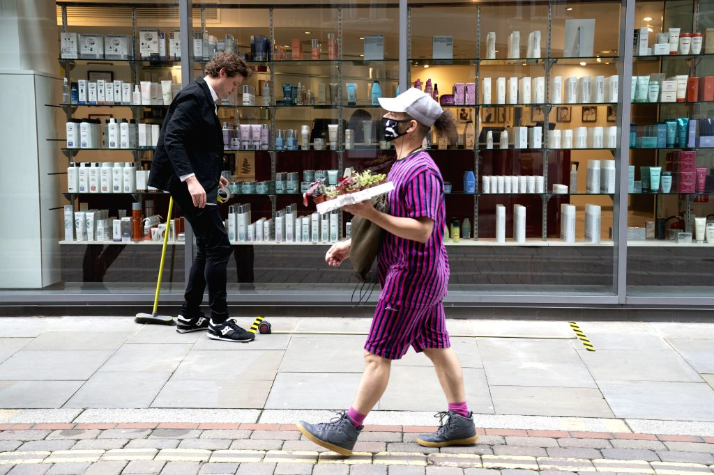 Salon creative director Lee Nunn (L) places safety markings outside for the reopening of Sassoon's Salon in Manchester, Britain on July 2, 2020. British Prime ... - Lee Nunn