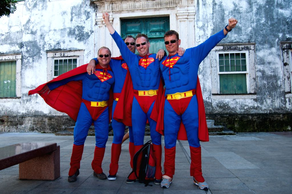 Germany's fans dressed up as Supermen pose for photos before a Group G match between Germany and Portugal of 2014 FIFA World Cup near the Arena Fonte Nova