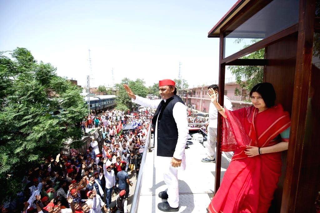 Samajwadi Party President Akhilesh Yadav and her wife and the party's Lok Sabha candidate from Kannauj Dimple Yadav wave at supporters during a roadshow ahead of the 2019 Lok Sabha elections in Uttar Pradesh's Kannauj on April 27, 2019. Kannauj is on - Akhilesh Yadav and Kannauj Dimple Yadav