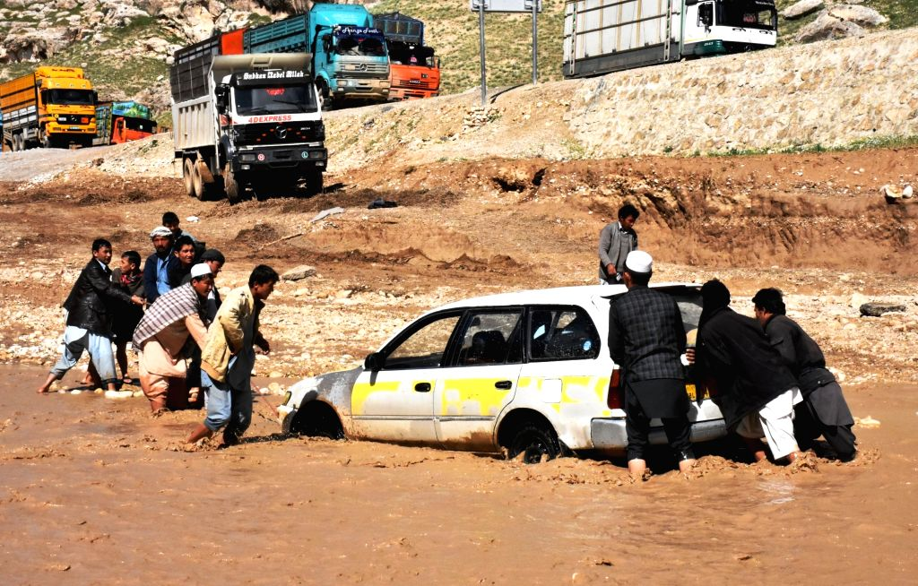SAMANGAN, April 17, 2016 - Afghan men push a car trapped in flood water after a heavy rain in Samangan province, northern Afghanistan, April 17, 2016. Heavy rainfall and floods claimed the lives of ...