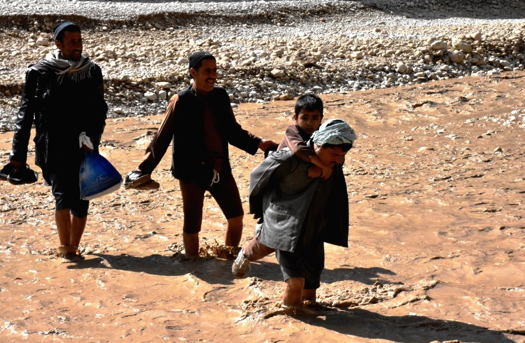 SAMANGAN, April 17, 2016 - Afghan men wade through flood water after a heavy rain in Samangan province, northern Afghanistan, April 17, 2016. Heavy rainfall and floods claimed the lives of 23 people ...