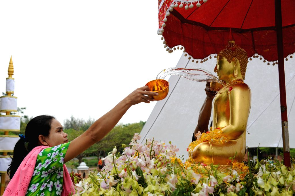 A Thai woman pours water onto a Buddha statue during a celebration of the upcoming Songkran Festival, Thailand's traditional New Year Festival, in Samut ...