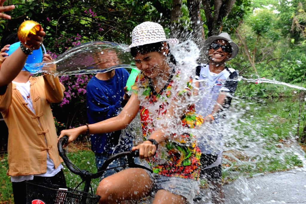 Thai people pour water on a cyclist during a celebration of the upcoming Songkran Festival, Thailand's traditional New Year Festival, in Samut Prakan, ...