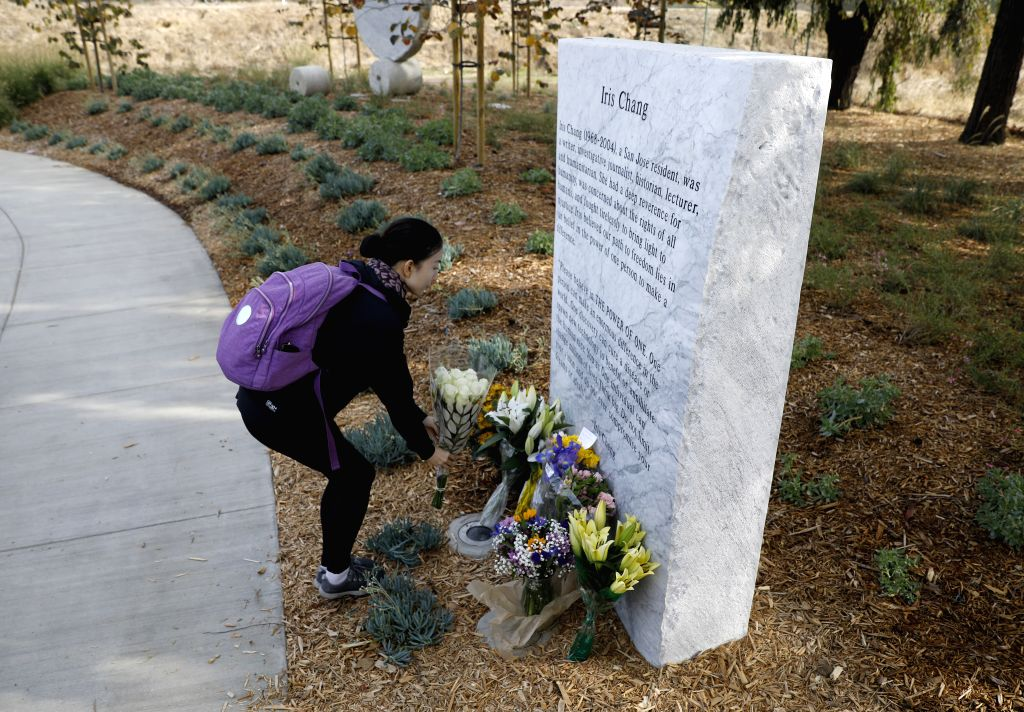 SAN FRANCISCO, Nov. 10, 2019 - A visitor presents a flower bouquet in front of a tablet inscribed with an introduction of Iris Chang at a memorial park named after the late Chinese-American writer in ...