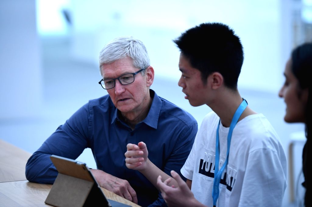 SAN JOSE, June 4, 2019 - Apple's Chief Executive Officer (CEO) Tim Cook (L) communicates with Wang Ziheng, a scholarship winner of the Worldwide Developers Conference at the San Jose Convention ...