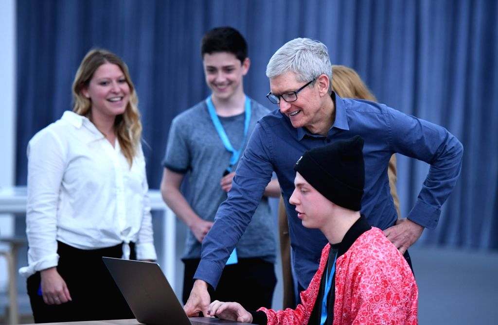 SAN JOSE, June 4, 2019 - Apple's Chief Executive Officer Tim Cook (3rd L) communicates with a scholarship winner of the Worldwide Developers Conference at the San Jose Convention Center in San Jose, ...