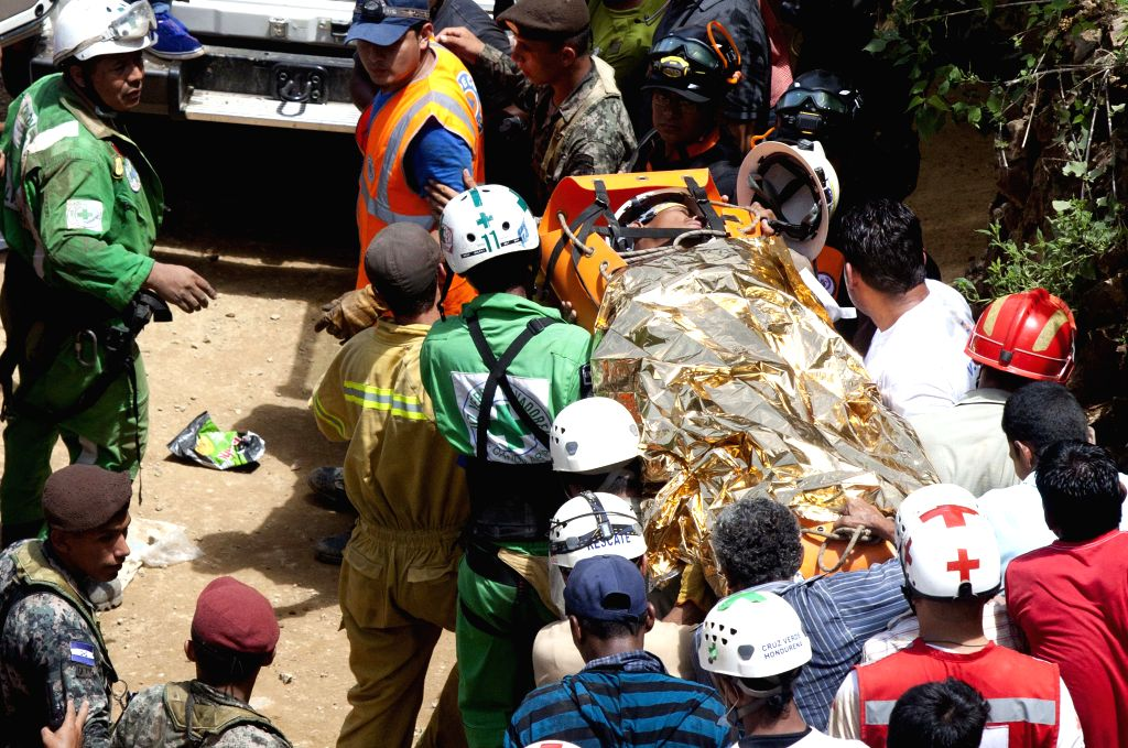 Rescuers carry a survivor to an ambulance after a collapse in an artisanal gold mine in San Juan Arriba, municipality of El Corpus, in Choluteca department, .
