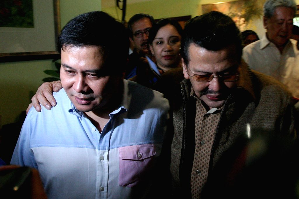 Philippine Senator Jinggoy Estrada (L) walks with his father, former President and current Mayor of Manila Joseph Estrada (R), at their home in San Juan City,