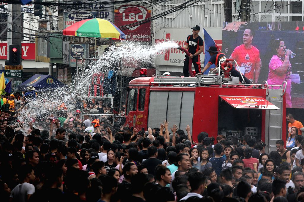 """SAN JUAN CITY, June 24, 2016 - Firefighters douse revelers with water from their fire truck during the """"Wattah-Wattah Festival"""" in San Juan City, the Philippines, June 24, 2016. The ..."""