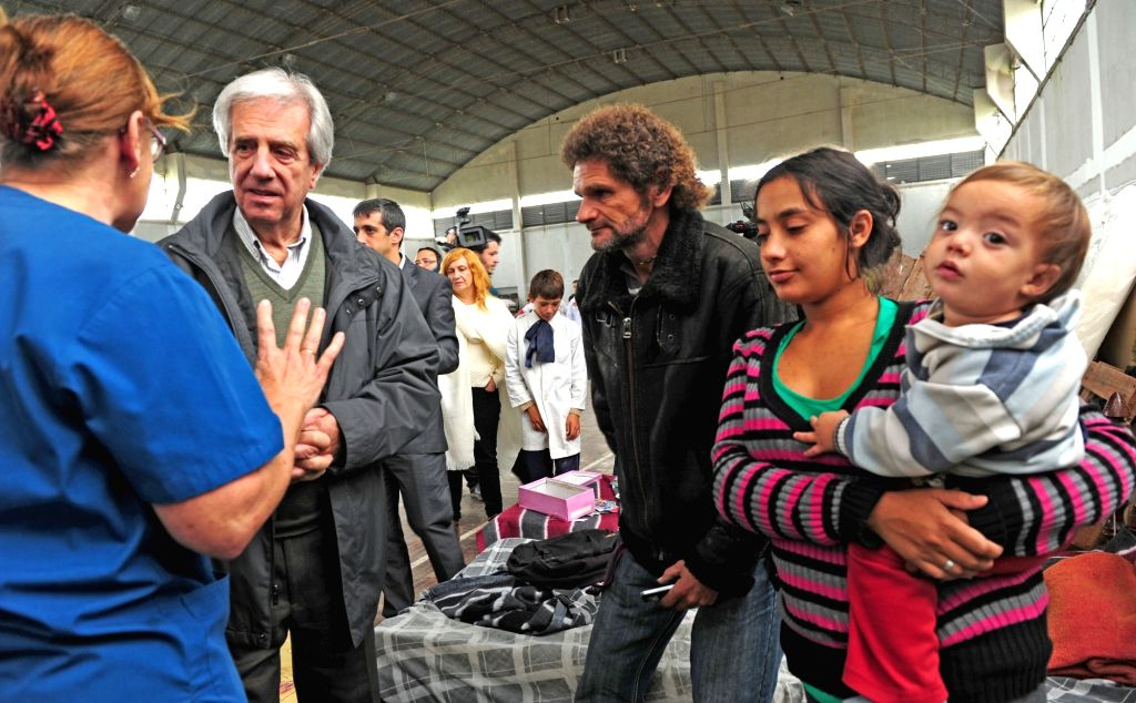 SAN RAMON, April 21, 2016 - Photo provided by Uruguay's Presidency shows Uruguayan President Tabare Vazquez (2nd L) talking with a woman during his visit to the flooded zone in San Ramon, Canelones ...