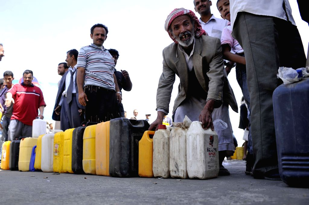 People line up to buy petrol at a gas station in Sanaa, Yemen, April 21, 2014. Frequent attacks on Yemen's oil pipelines have caused reduction in oil export and fuel