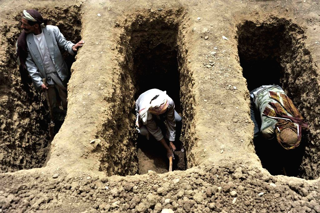 Yemeni men dig graves for the victims in Saudi-led air strikes in Bani Matar district, about 70 km west of capital of Sanaa, Yemen, April 4, 2015. Nine civilians, ...