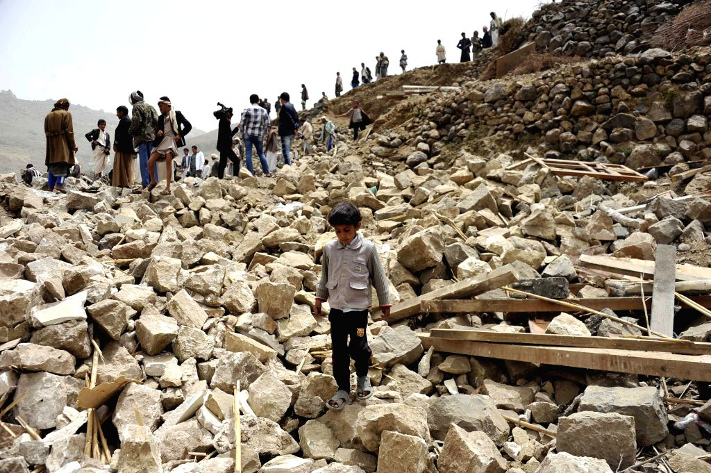 Yemenis stand on the rubbles of a house which was destroyed during Saudi-led air strikes in Bani Matar district, about 70 km west of capital of Sanaa, Yemen, April 4, ...