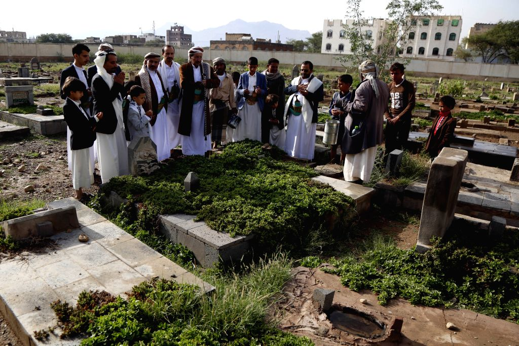 SANAA, Aug. 11, 2019 - People mourn for their relatives at a cemetery during the first day of  Eid al-Adha in Sanaa, Yemen, on Aug. 11, 2019.