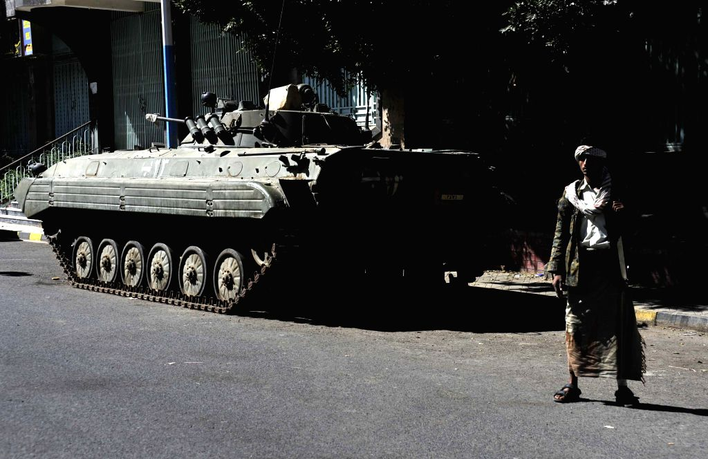A fighter of the Shiite Houthi group patrols outside the presidential palace where the revolutionary committee held a meeting in Sanaa, Yemen, Feb. 16, 2015. The ...
