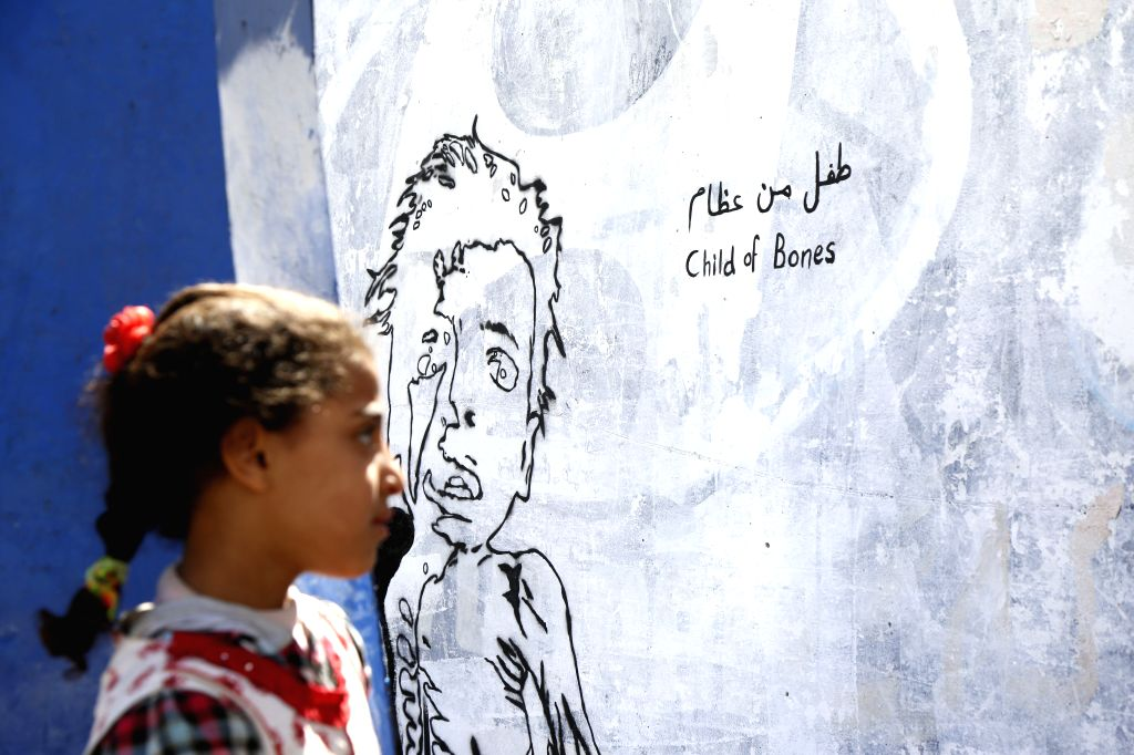 "SANAA, Feb. 21, 2019 - A girl looks at graffiti titled ""Child of Bones"" on a wall in Sanaa, Yemen, Feb. 21, 2019. A graffiti campaign by Yemeni artists was staged to call for the world's ..."