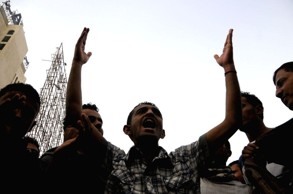 Yemeni protesters shout slogans during a rally to support Yemen's outgoing President Abd-Rabbu Mansour Hadi in Sanaa, Yemen, Feb. 23, 2015. After almost one-month ...