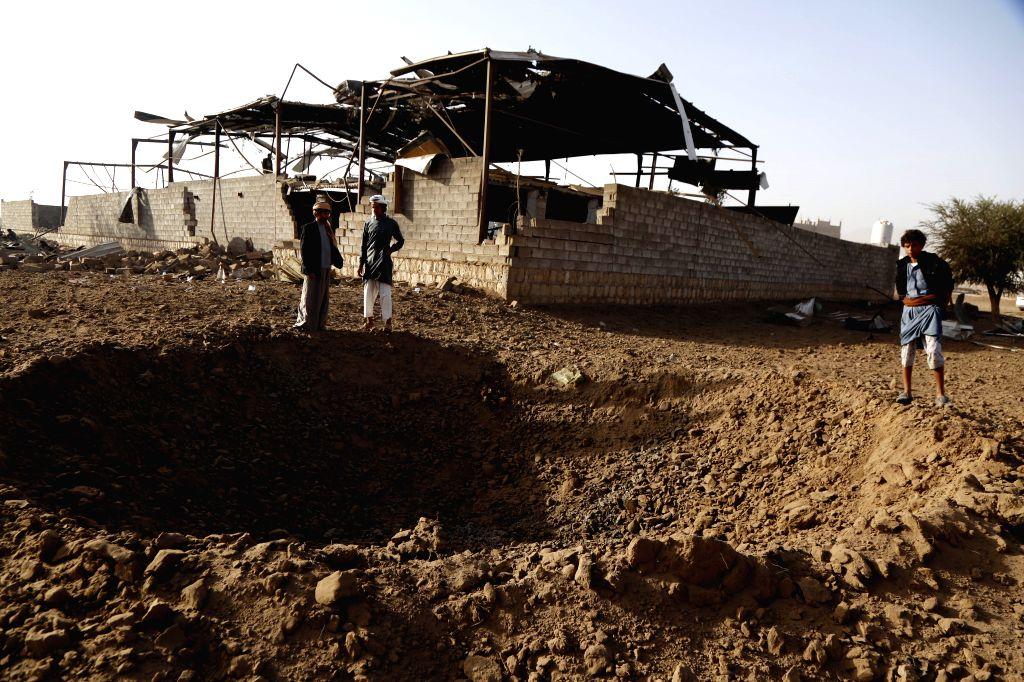 SANAA, Jan. 20, 2019 - Men stand above a hole made by an airstrike last midnight in Sanaa, Yemen, on Jan. 20, 2019. Four powerful Saudi-led coalition airstrikes hit Yemen's rebel-held capital Sanaa ...