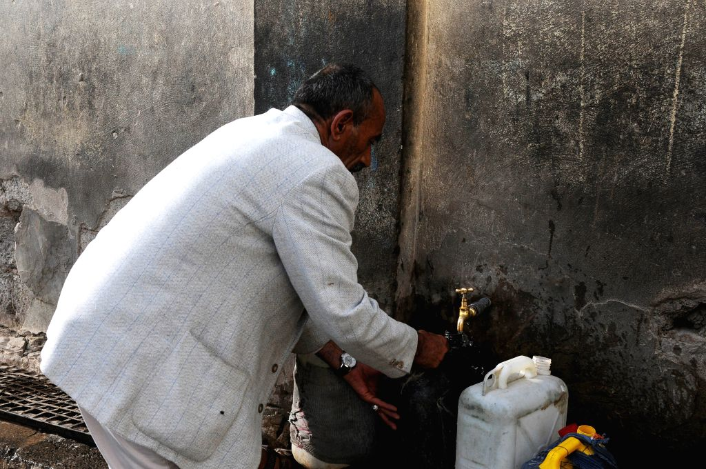 SANAA, July 24, 2018 - A man collects clean water to his bottle from a free water pump during a clean running water crisis in Sanaa, Yemen, on July 24, 2018. According to the World Health ...