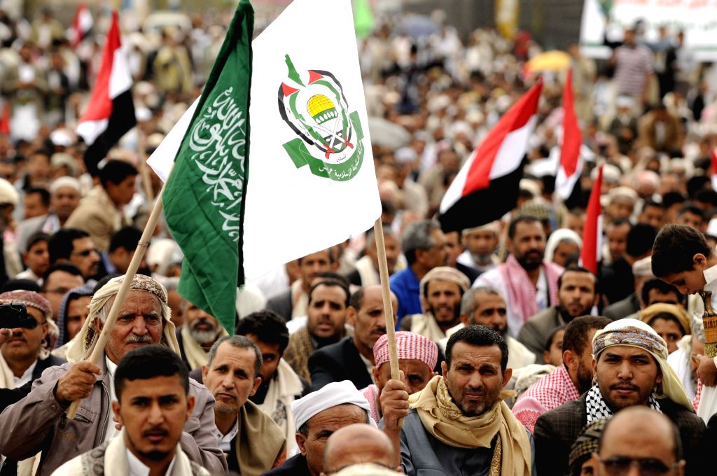 Yemeni protesters wave the Palestinian flag and Hamas flag when they take part in a demonstration against the Israeli attack on Gaza, in Sanaa, Yemen, on July 25, ...