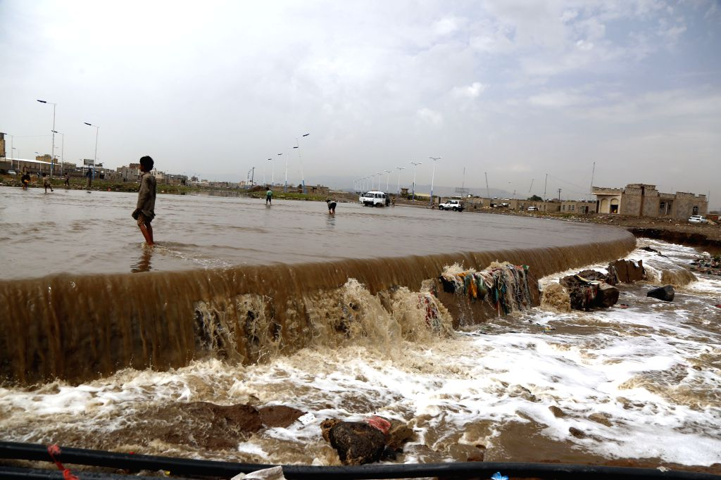 SANAA, July 27, 2019 - People walk in flood torrent after heavy rain in Sanaa, Yemen, July 26, 2019. Heavy rains and flood frequently hit many governorates in Yemen this summer. (Photo by Mohammed ...