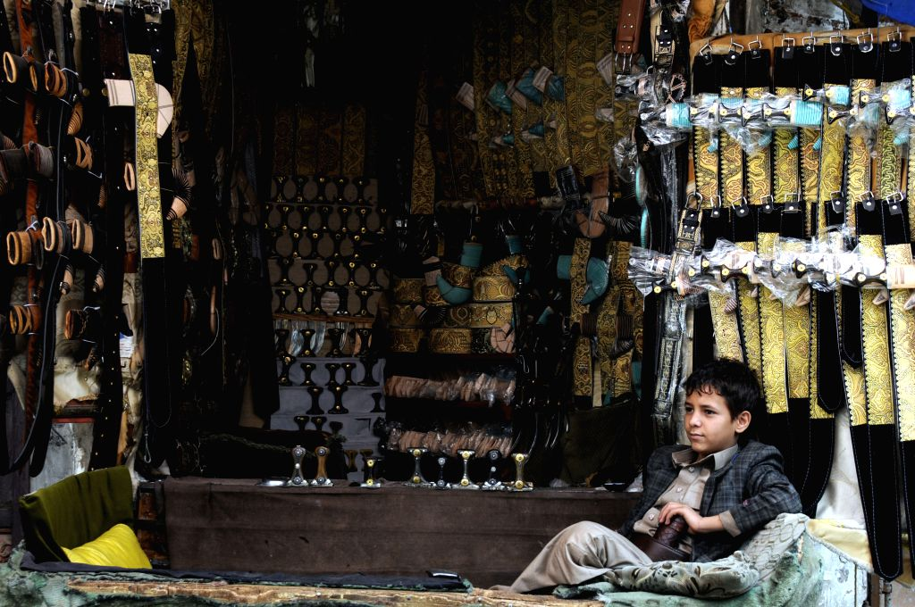 SANAA, July 29, 2016 - A child waits for customer at his father's shop selling the traditional daggers, at the Yemen's historical Old City of Sanaa, July 29, 2016.