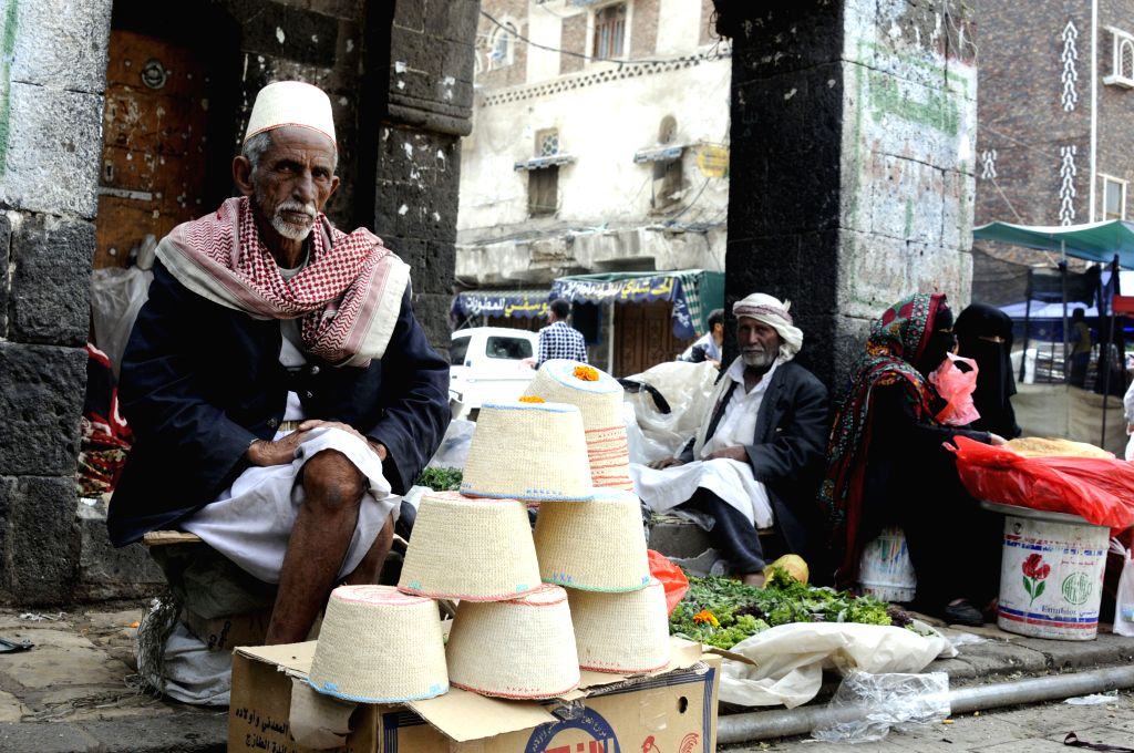 SANAA, July 29, 2016 - A man sells hay-made caps (L) waits for customer at the Yemen's historical Old City of Sanaa, July 29, 2016.