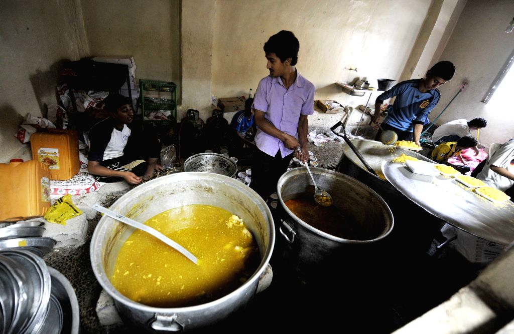 Yemeni men prepare meals to be distributed to the poor people in Sanaa, Yemen, July 4, 2014. During the holy month of Ramadan, Muslims give charity, for example free ..